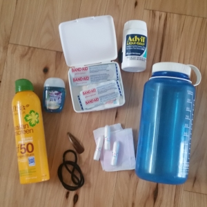 Various items like sunscreen, water bottle, first aid