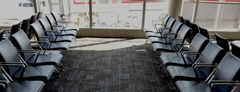 Empty chairs at an airport with a plane in the background