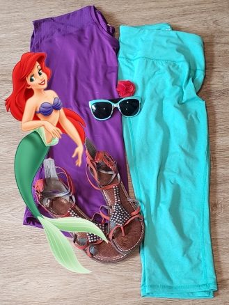 Purple shirt folded in half lays next to teal leggings. A red hair pin, teal sunglasses, and orange sandals are on top of them. A cartoon of Ariel is overlaid on the clothing.