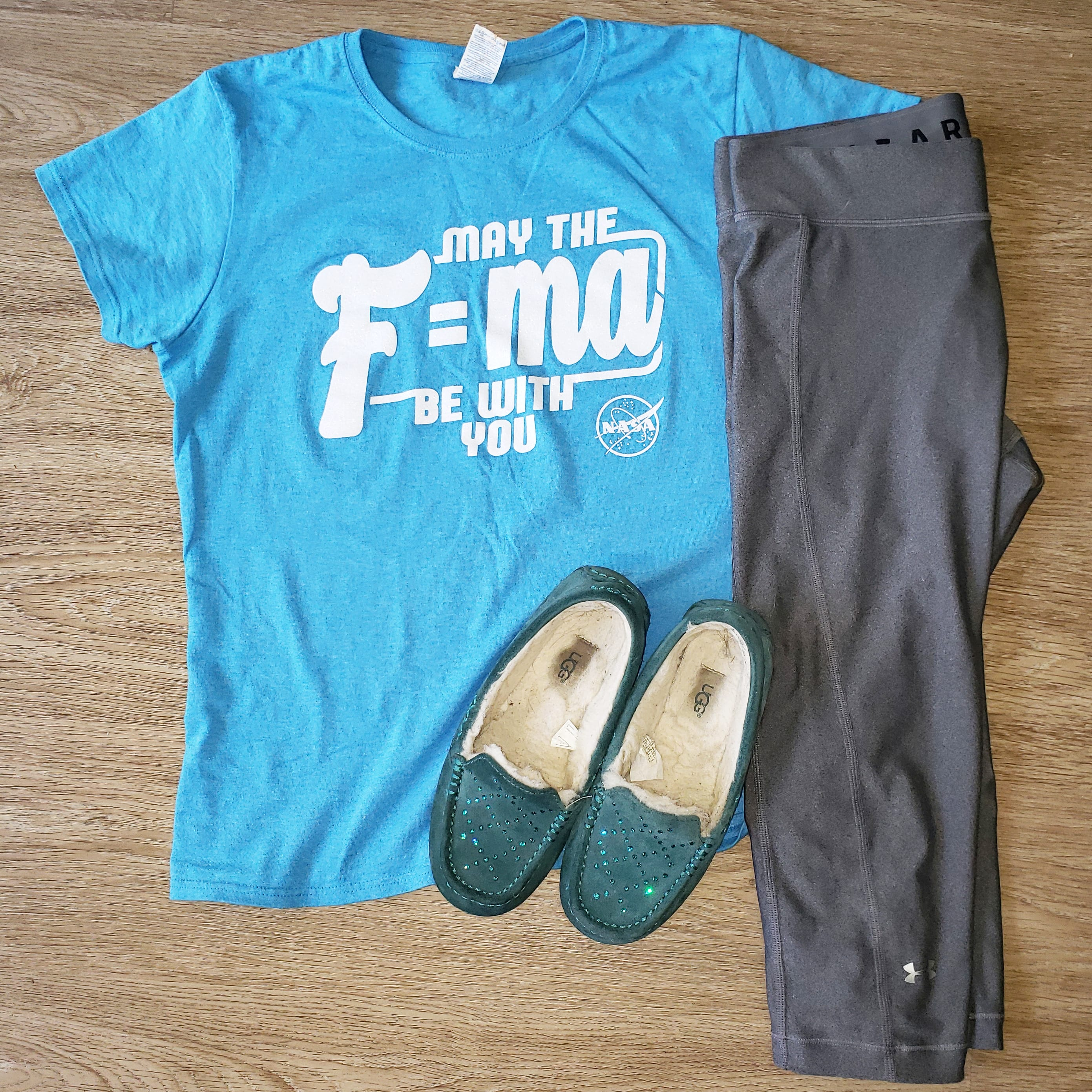 A bright blue shirt reads May the F=ma be with you in sparkling white text. Gray leggings and teal slippers are next to the shirt.
