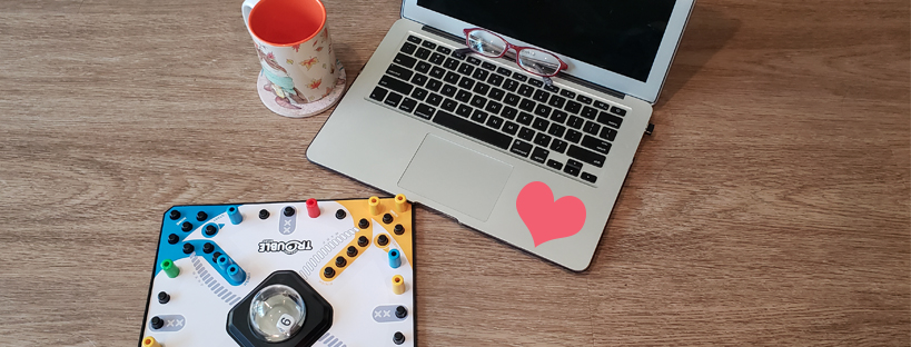 On a wood desk, the game Trouble is set up in front of a laptop with a heart and glasses on it. Next to the laptop is a fall theme mug.