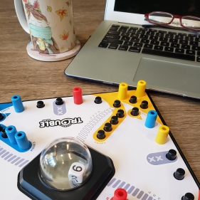 On a wood desk, a mug, the game Trouble, and a laptop with glasses are set up ready to play.