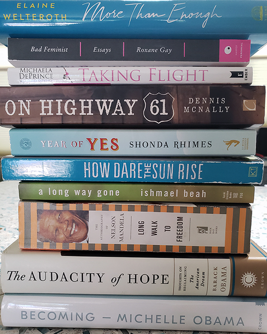 Stack of books: Becoming, The Audacity of Hope, Long Walk to Freedom, A Long Way Gone, How Dare the Sun Rise, Year of Yes, On Highway 61, Taking Flight, Bad Feminist, More than Enough