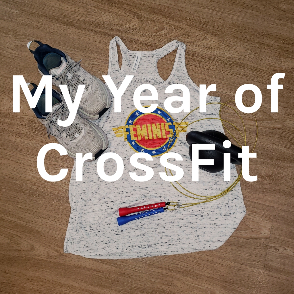 """A black kettle bell, a Wonder Woman themed jumprope, and sneakers sit on top of a racerback tank top that reads """"Feminist"""" style like the Wonder Woman icon. """"My Year of CrossFit"""" overlays the image."""