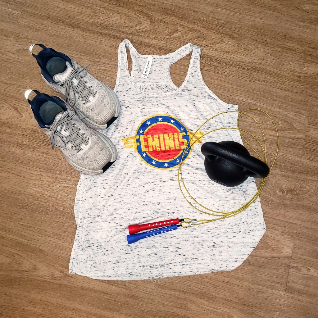 """A black kettle bell, a Wonder Woman themed jumprope, and sneakers sit on top of a racerback tank top that reads """"Feminist"""" style like the Wonder Woman icon."""