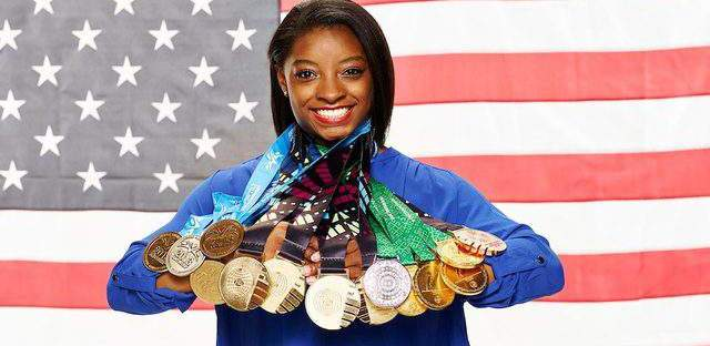 Simone Biles wearing all of her career medals stands in front of the flag of the United States.