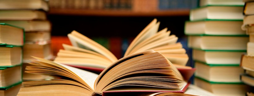 In a library, a few books are open on a table with stacks of books next to them.