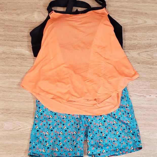 An outfit lays on the ground. The shorts are teal with birds and leaves. The shirt is bright orange, with a black bra behind it.
