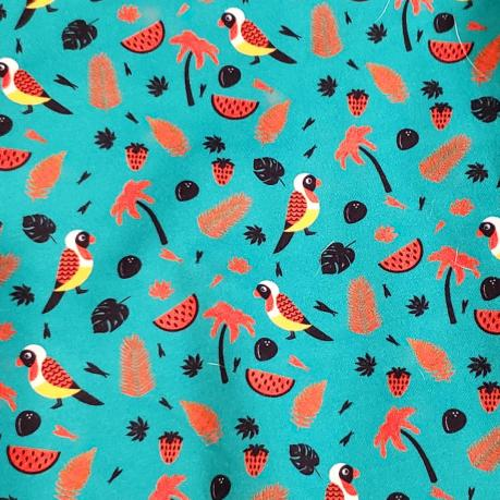 This patterned cloth has birds, stawberries, orange leaves, watermelon slices, and orange palm trees on it.